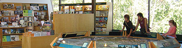 Three visitors explore the 3-D map of the island at the visitor center. Books are on display in the sales area.