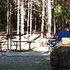 Wooded campsite includes tent, fire grate, and picnic table.