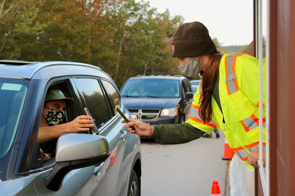 Park staffer uses mobile device to check a visitor's vehicle reservation