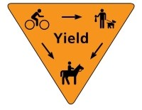 Orange yield sign with pedestrian, bicycle, and horse