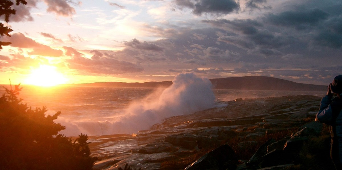 sun sets on right as ocean wave crash on rocks, mountains in background