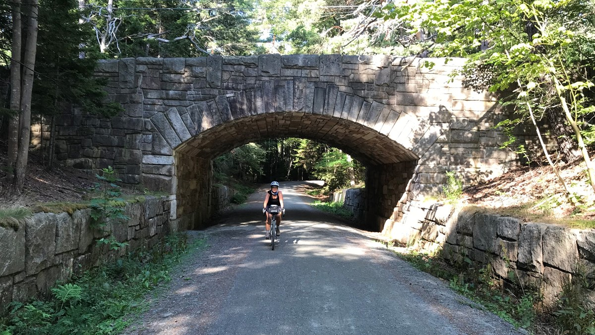 A bicyclist wearing a helmet rides under a carriage road bridge