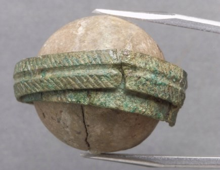 A clay ball with a copper-alloy band.