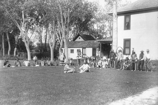 A meeting between James Cook and Jack Red Cloud on the lawn in front of the ranch house.