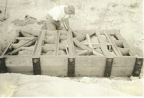 A worker building a crate around a bonebed slab in the early 1900's.