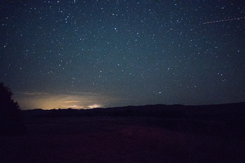 Photo of night sky with shooting star and sunset light on horizon.