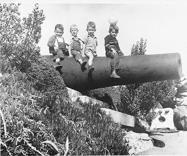 Children posing on obsolete army cannon