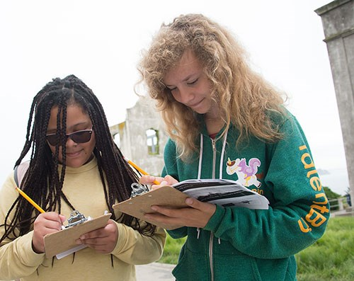 Two students write on clip boards at Alcatraz