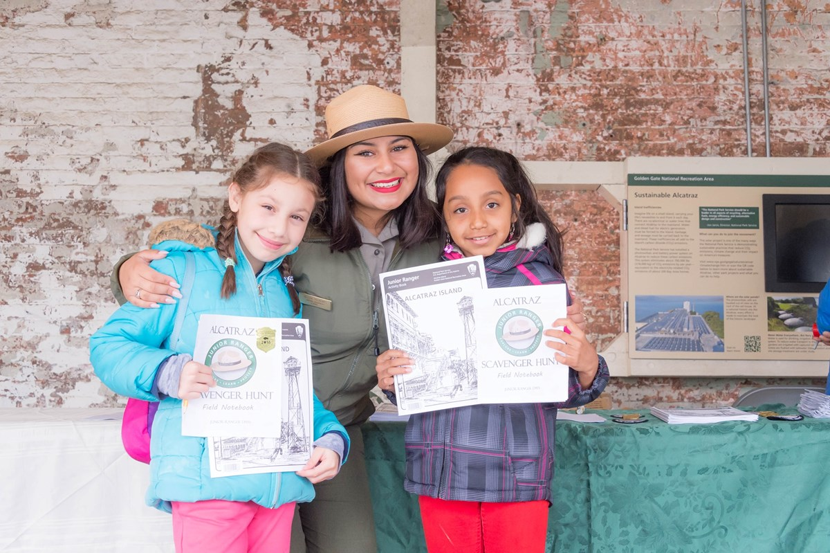 Park Ranger stands between two girls holding Junior Ranger Books.