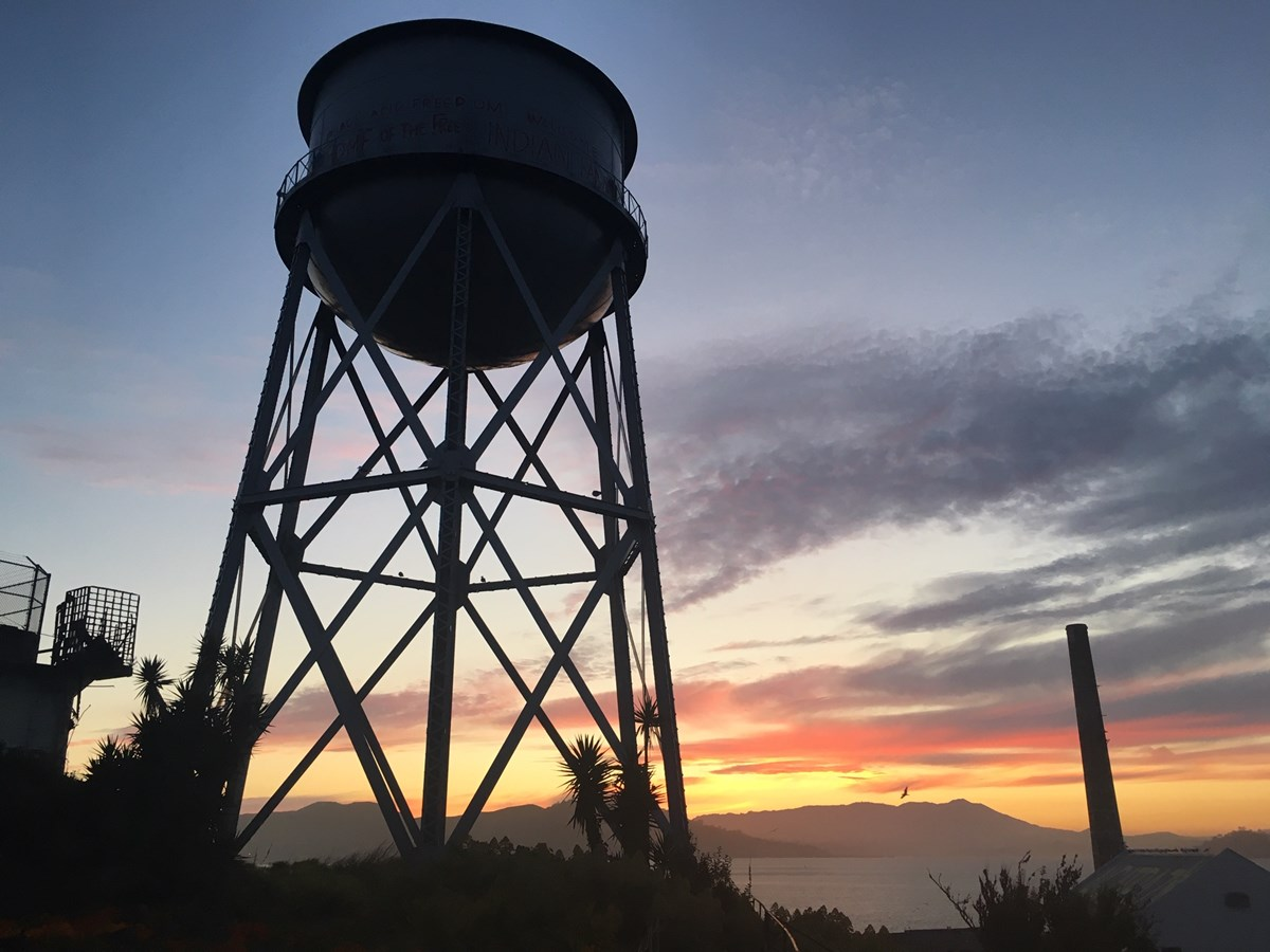 The Alcatraz water tower silhouetted against the sunset.