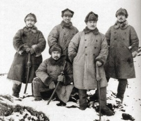Historic photo of five Japanese men posing in winter coats and hats