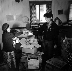 Black and white image of a woman and man standing in room cluttered with open cardboard boxes and papers.
