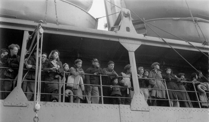 black and white photo of people lining the edge of a boat