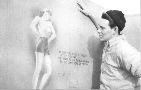 George Sproul (ARM) observes the fuselage nose art on one of the squadrons planes