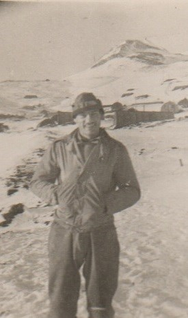 A man in uniform stands in the snow