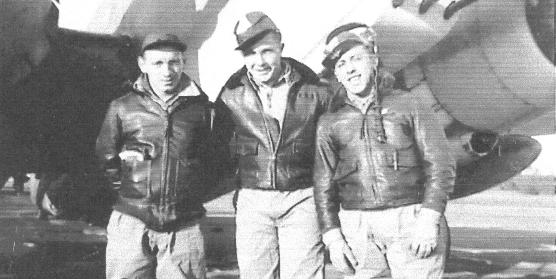 Three men in front of a plane