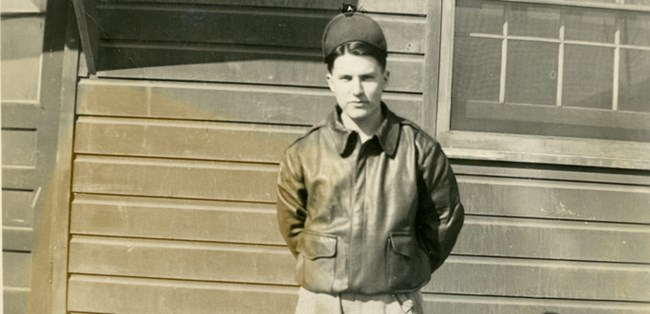 A black and white photo of a man facing the camera in a bomber jacket and hat.