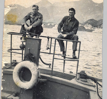 Historic image of two men sitting on the railing of a boat, mountains in the background