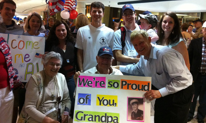multi-generational family surrounding two elderly individuals with signs and balloons