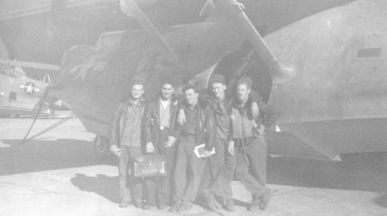 Crewmembers stand in front of their plane