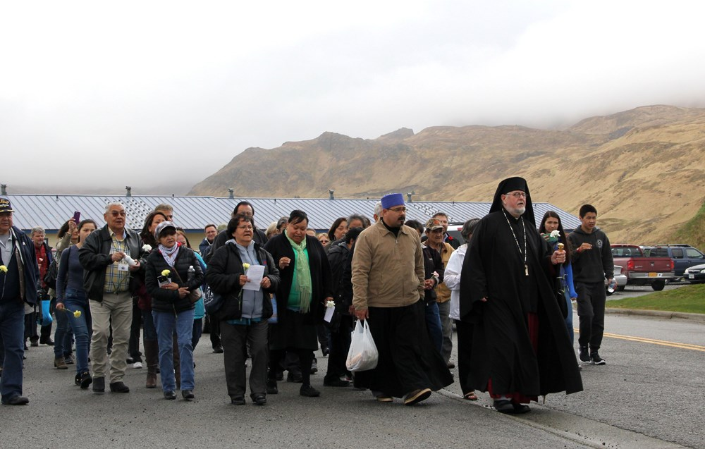 Group of people led by a bishop in front of mountains