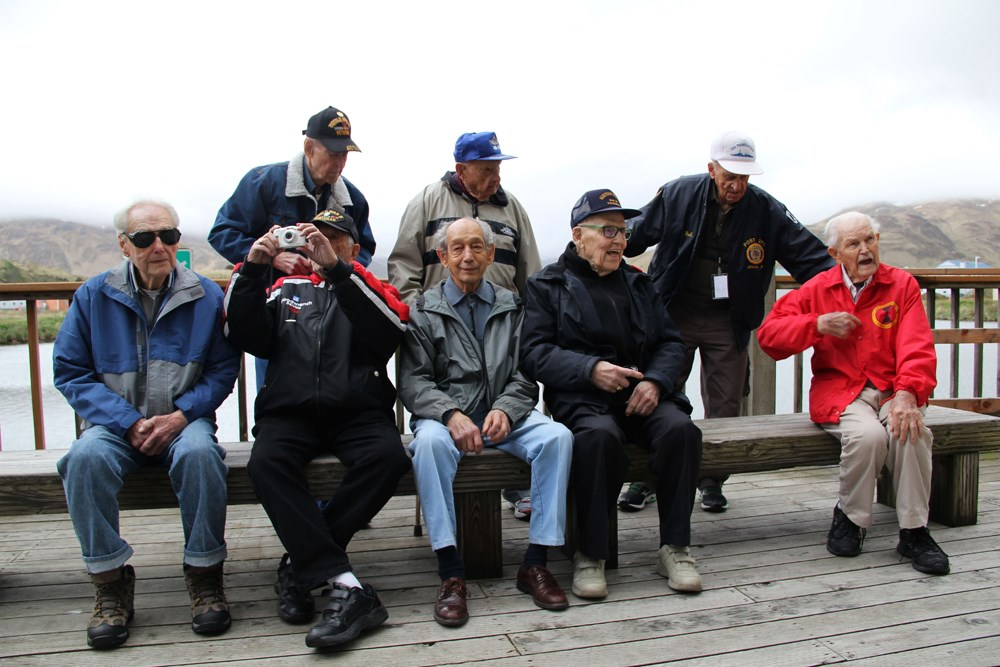Eight men pose for a photo on a porch