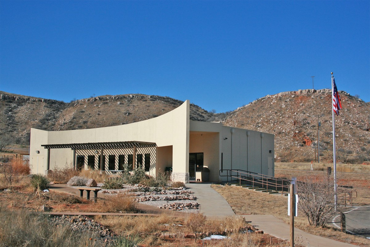 Alibates Flint Quarries Visitor Center with with path leading to building and hills behind.