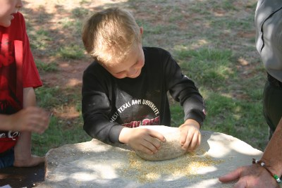 Grinding corn on a metate.