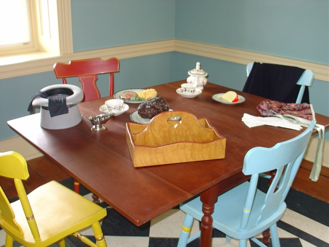 Photo of a table set as if travelers had just left. All items reproduction.