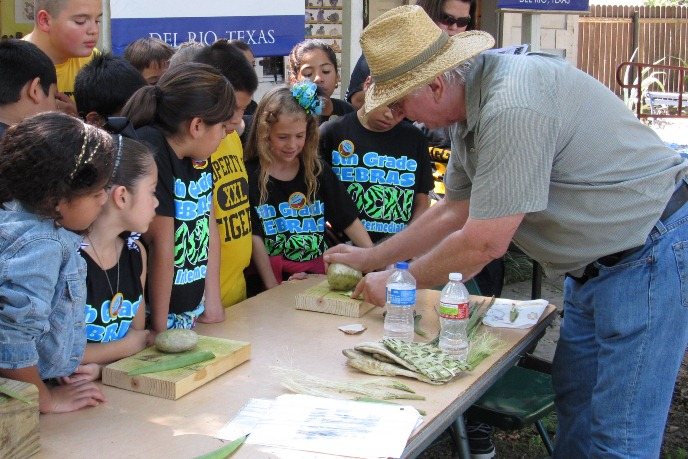 volunteer demonstrating to students how to make cordage from plant fibers at Archeology Fair.