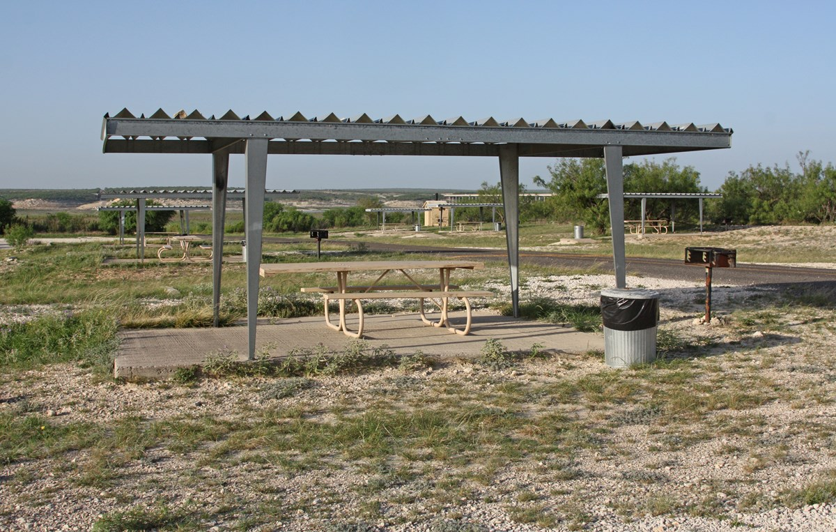 Covered picnic table at campsite in desert landscape.