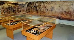 Replica of Native American artifacts in exhibit cases and scaled wall photograph of rock art.