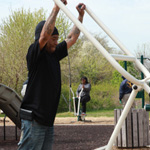 People use exercise equipment in the park.
