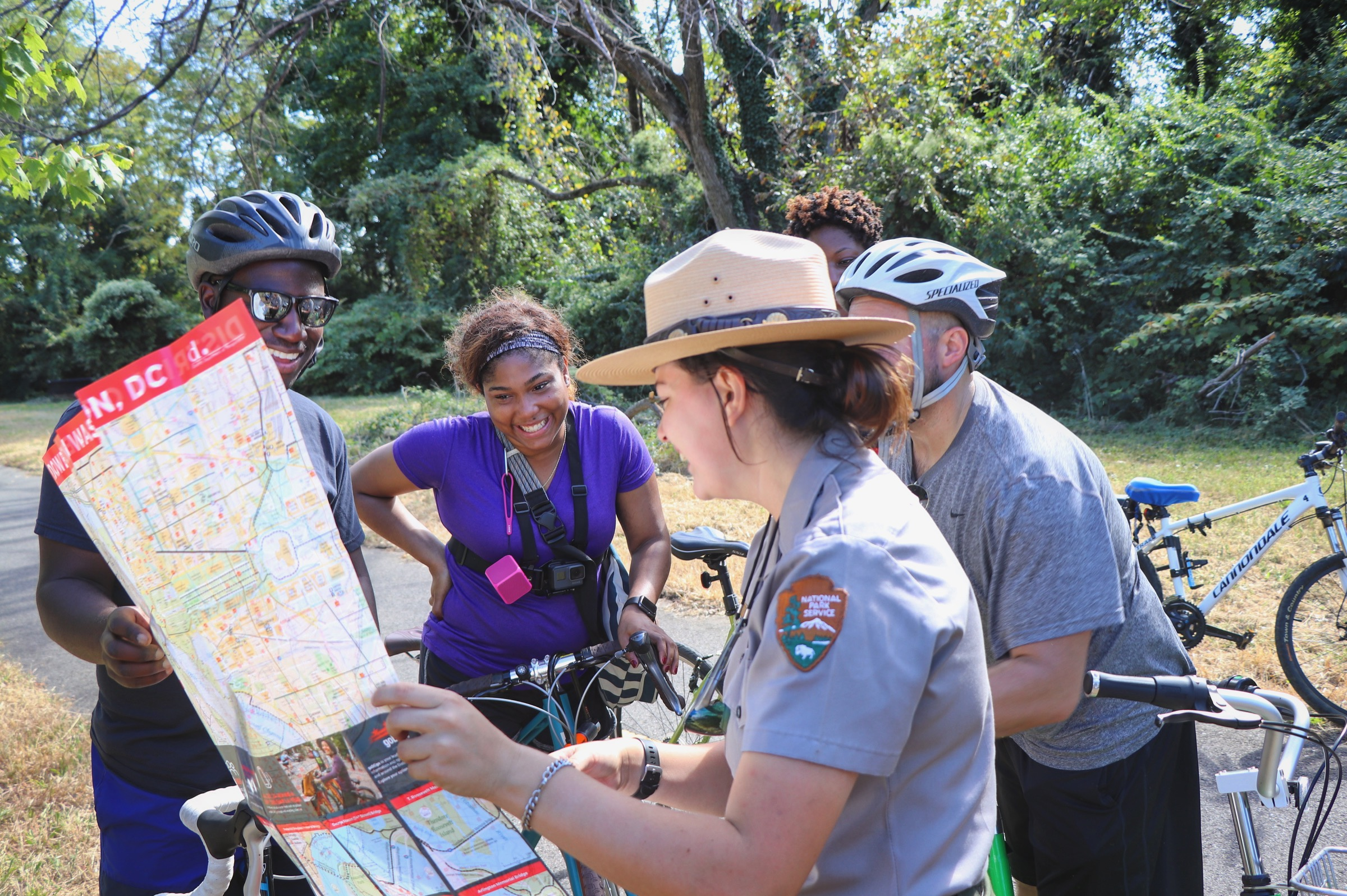 Park ranger provides directions with map to visitors on bikes on the Anacostia Riverwalk Trail