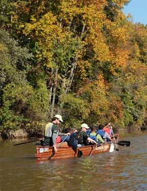 A group of people paddle a large canoe.