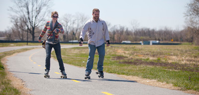 A man and woman smile as they roller skate on a paved trail by the Anacostia River.
