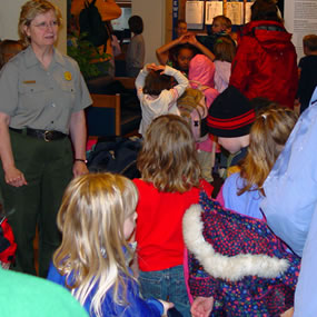 Kids on a field trip in the visitor center with a park ranger.