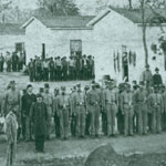 Confederate soldiers lined up for roll call in a Federal military prison
