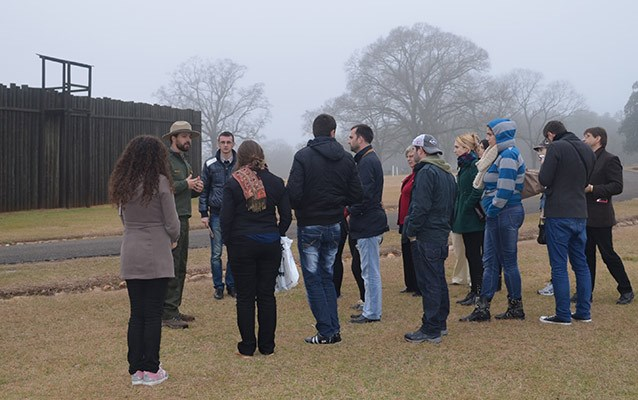 Park ranger leads college students in a discussion in front of the stockade wall
