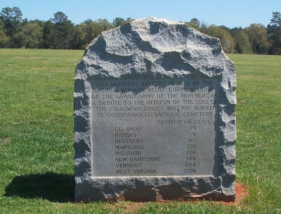 A stone monument with text octaed in a grassy field.