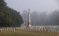 A tall monument topped by a soldier statue is surrounded by graves.