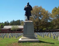 Stone and Bronze monument of a Civil War soldier surrounded by white headstones