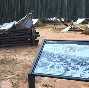 Reconstructed prison corner with replica shelters and wayside exhibit panel