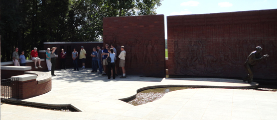 A park ranger speaks to visitors in a brick lines courtyard space