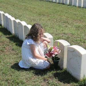 Young girl kneeling next to a grave decorated with flowers.