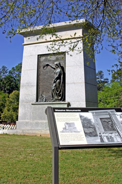 A tal granite monument rises in the distance, with an exhibit panel in the foreground.