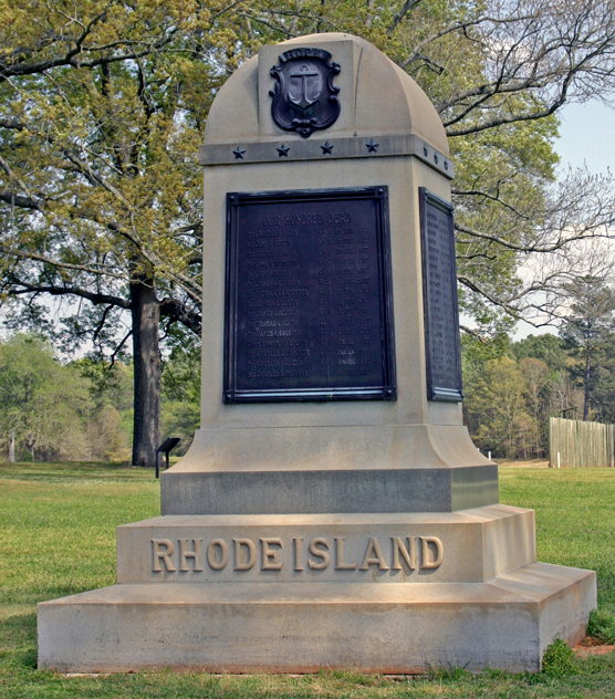 "A stone monument with aplaque and the words ""Rhode Island."""
