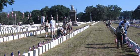 Scouts and leaders placing flags in the National Cemetery