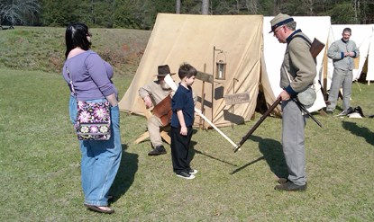 A boy with a wooden musket practices rifle drill with a Civil War soldier.