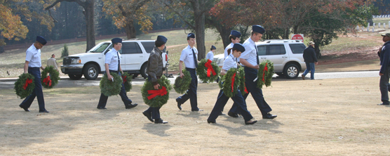 Young men in uniform carrying Christmas Wreaths